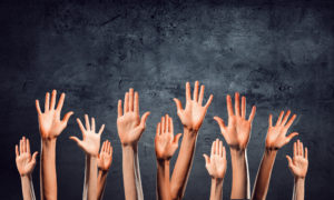 the raised hands of people who want virtual healthcare